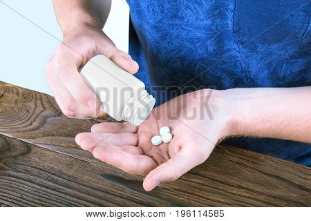 Man's hands holding a bottle of pills on a bright gray background. A man in a saturated blue shirt taking prescripted drugs next to a brown wooden table. A white bottle of painkillers and antibiotics.