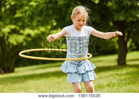Girl makes gymnastics with tire in summer at the park