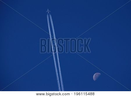 Modern airplane crossing the intense blue sky beside the waning moon