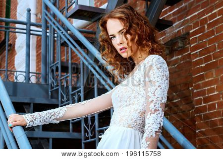Beautiful young woman with bright foxy hair wearing evening white dress on a city street. Charming bride woman posing outdoor. Urban fashion.