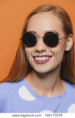Joyful young woman with beautiful smile posing over yellow background. Happiness, summer concept. Sunglasses. Copy space.