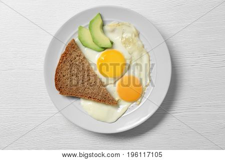 Delicious breakfast with over easy eggs on wooden background