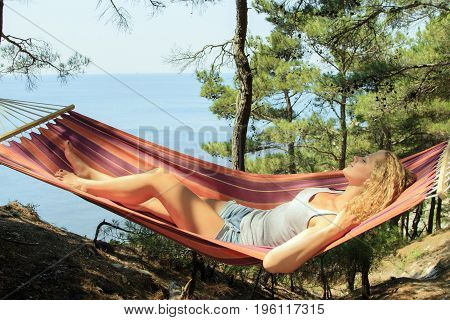 Beautiful young girl resting in a hammock