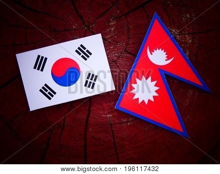 South Korean Flag With Nepali Flag On A Tree Stump Isolated