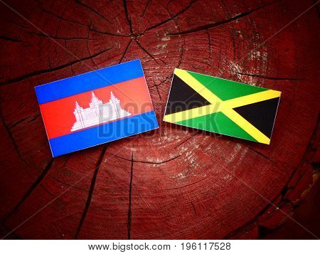 Cambodian Flag With Jamaican Flag On A Tree Stump Isolated