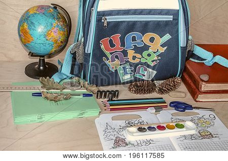 Exercise bookpencils paints scissors and blue backpack with letters first school supplies