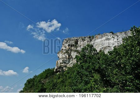 Stunning Mountain Surrounded By Forest With A Blue Sky On The Background.
