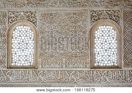 Detailed closeup view of decorated wall with 2 windows, Alhambra, Andalusia, Spain