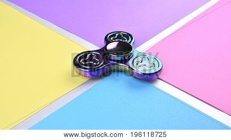 Hand fidget spinner toy on colorful and trendy background. Stress and anxiety relief.