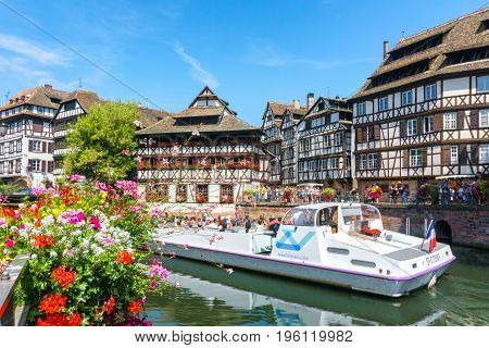 STRASBOURG FRANCE - JUL 18 2017: Traditional colorful houses in La Petite with tourists taking a boat ride along traditional colorful houses on idyllic river Lauch in summer Colmar Alsace France