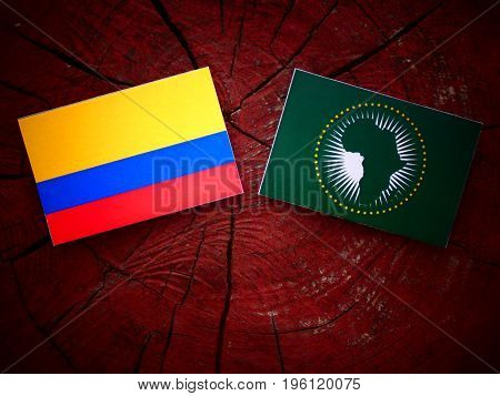 Colombian Flag With African Union Flag On A Tree Stump Isolated