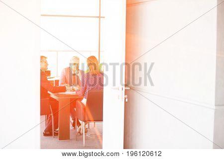 Businessmen and businesswoman in board room seen through open door at office