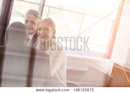 Smiling young businesswoman with male colleagues in meeting room