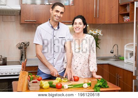 couple cooking in kitchen interior with fresh fruits and vegetables, healthy food concept, pregnant woman and man