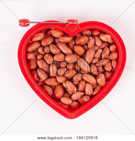 Raw peanuts in heart bowl on the white background