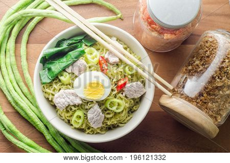 Instant vegetable noodles in a bowl on wooden background.