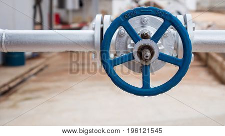 Close up of manual operate ball valve at factory. Pipes and valves industrail equipment.