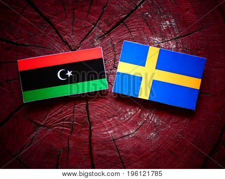 Libyan Flag With Swedish Flag On A Tree Stump Isolated