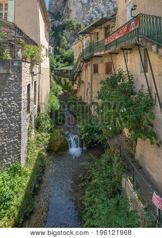 MOUSTIERS-SAINTE-MARIE FRANCE - JUNE 20, 2017: River and small waterfall at  amazing medieval town Moustier-Sainte-Marie, France