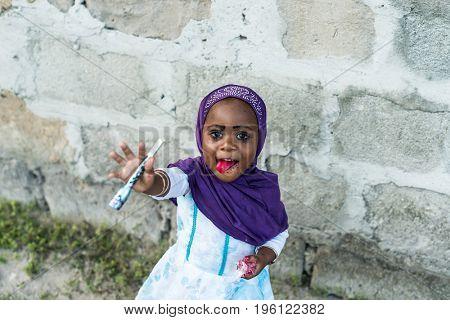 Zanzibar, Tanzania - July 15, 2016: Little muslim child of zanzibar wearing bright violet burka and reaching her arms, smiling