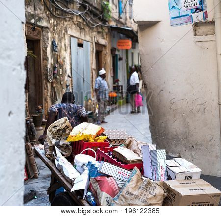 Zanzibar, Tanzania - July 15, 2016: Man pulling huge overloaded pushcart full of garbage and some wrapped goods, narrow street, zanzibar