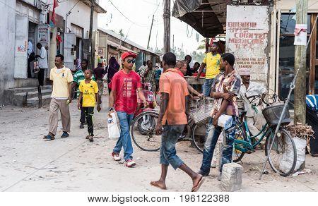 Zanzibar, Tanzania - July 15, 2016: Busy street on zanzibar, tanzania,people walking and chatting, marketplace, bicycle parked nearby
