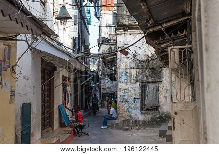 Zanzibar, Tanzania - July 15, 2016: Small houses of locals of zanzibar, people sitting in the street, dirty buildings