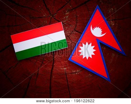 Hungarian Flag With Nepali Flag On A Tree Stump Isolated