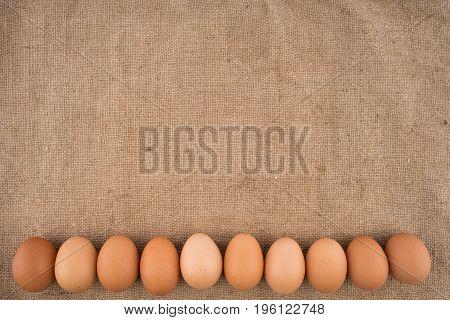 Chicken eggs on brown burlap. Top view.