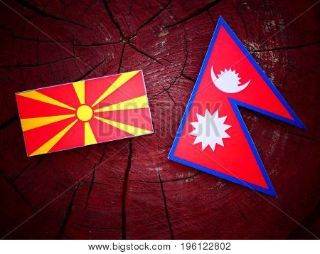 Macedonian Flag With Nepali Flag On A Tree Stump Isolated