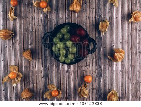 Fresh juicy group of organic physalis, green grapes and gooseberries in black bowl on wooden table. Flat lay style.