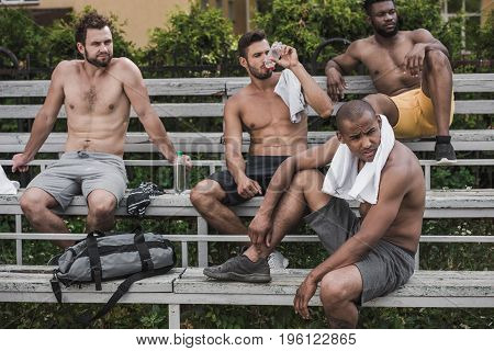 Group Of Young Handsome Sportsmen Sitting And Resting After Game