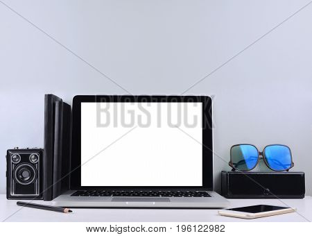 Stylish workspace with laptop computer, office supplies, camera at home or studio. Place for your text.