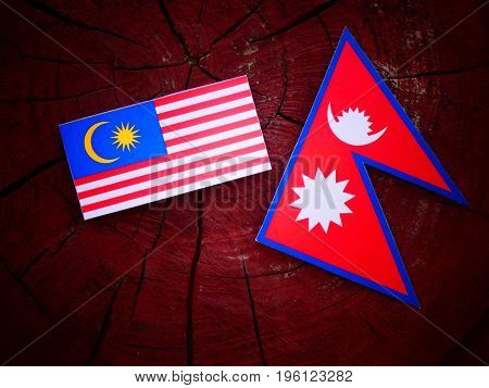 Malaysian Flag With Nepali Flag On A Tree Stump Isolated