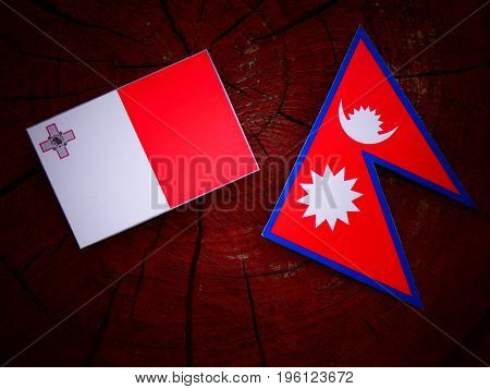 Maltese Flag With Nepali Flag On A Tree Stump Isolated