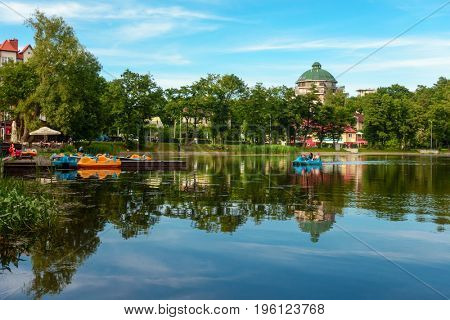 Svetlogorsk, Russia - July 14, 2017: People ride on boats and catamarans on the lake at summer day time