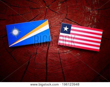 Marshall Islands Flag With Liberian Flag On A Tree Stump Isolated