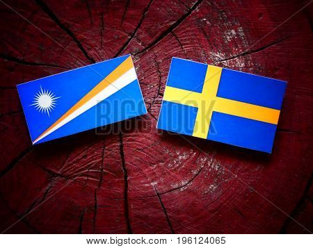 Marshall Islands Flag With Swedish Flag On A Tree Stump Isolated