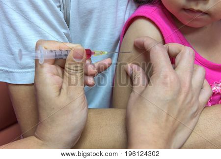Close-up hands nurses are vaccinations to children using the syringe. Doctor vaccinating women in hospital. Are treated by the use of sterile injectable upper arm. injection