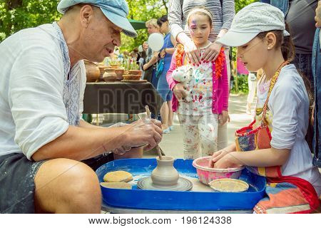 Zaporizhia/Ukraine- May 28, 2017: Charity Family festival: Outdoors pottery workshop - ceramist master explaining  girl how to make clay jug . Art and craft activity.