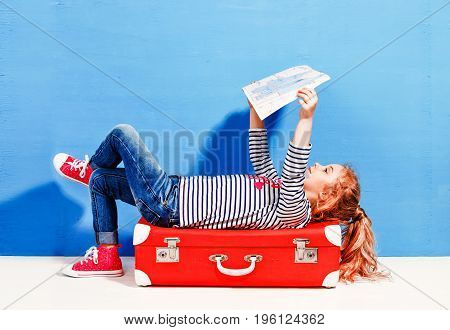 Child blonde girl with pink vintage suitcase and city map ready for summer vacation. Travel and adventure concept.