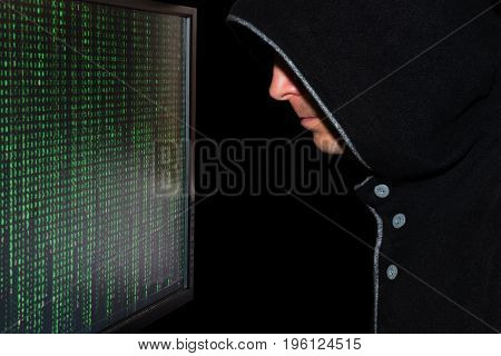 The hacker in the hood in front of the monitor screen with green code symbols