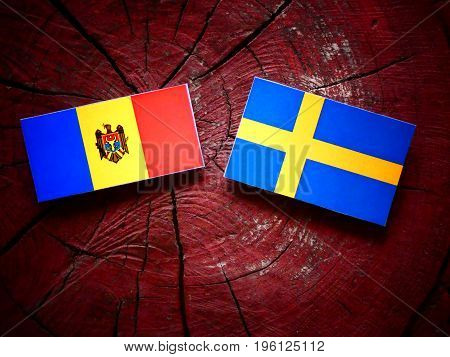 Moldovan Flag With Swedish Flag On A Tree Stump Isolated