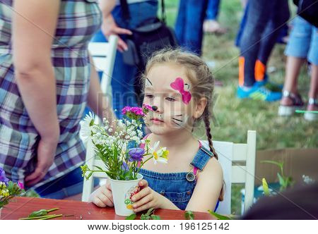 Zaporizhia/Ukraine- May 28, 2017: Charity Family festival:  Small girl with kitten mask face paint participating at outdoors florist workshop, admiring self made beautiful flowers arrangement. Art and craft children activity.