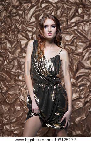 Portrait of alluring woman wearing glossy dress posing in the studio