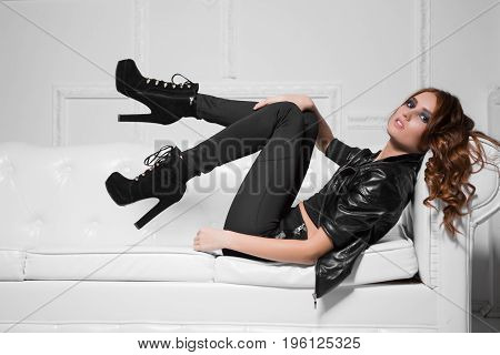 Sexy young lady wearing black fashionable clothes and high heels lying on the sofa
