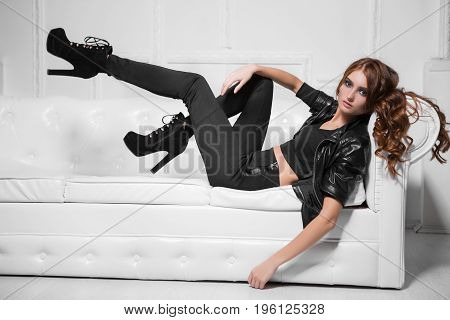 Leggy young lady wearing black fashionable clothes and high heels lying on the sofa