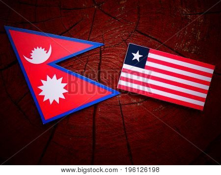 Nepali Flag With Liberian Flag On A Tree Stump Isolated