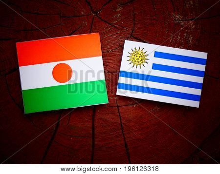 Niger Flag With Uruguaian Flag On A Tree Stump Isolated