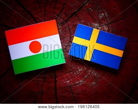 Niger Flag With Swedish Flag On A Tree Stump Isolated